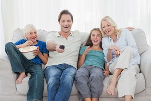 Family watching television sitting on sofa
