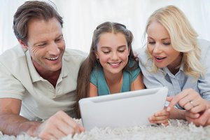 Girl and her parents using a tablet