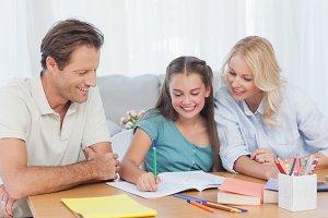 Parents helping her daughter doing her homework