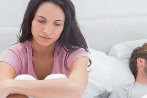 Thoughtful woman sat on her bed