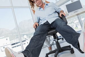 Smiling designers having fun with on a swivel chair