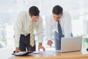 Businessmen working together leaning on desk