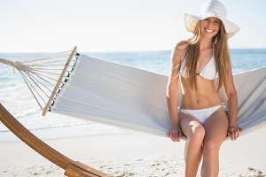 Pretty blonde wearing bikini and sunhat sitting on hammock and smiling