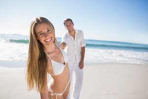 Woman smiling at camera with boyfriend holding her hand