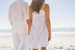 Attractive couple holding hands and walking to the water