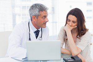 Serious docter showing something on laptop to his patient