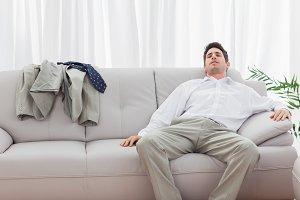 Tired businessman sitting back on sofa