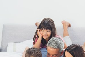 Happy family lying on bed using their laptop