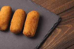 Croquettes on plate of slate seen from above. Horizontal shoot.