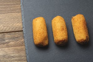 Close-up of several croquettes on slate plate. Horizontal shoot.