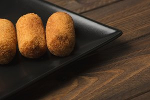 Close-up of several croquettes on black plate. Horizontal shoot.