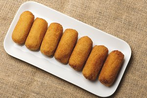 Croquettes in a white tray on cloth and brown wooden table. View from above. Appetizer