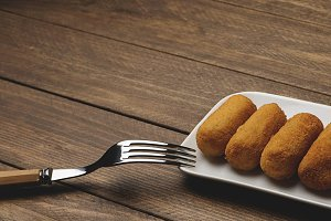 Croquettes on white tray next to a fork on brown wooden table. Horizontal shoot.