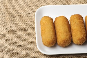 Close-up of croquettes in a white tray on brown fabric. Horizontal shoot. Appetizer