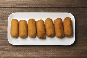 Croquettes in a white tray on brown wooden table. View from above. Appetizer