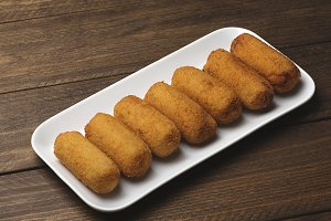 Croquettes in a white tray on brown wooden table. Appetizer.