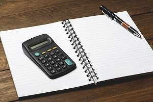 Office supplies with pen and calculator on brown wooden table.