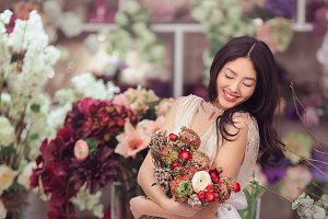 Beautiful asian woman florist in white dress with bouquet of flowers in hands in flower store