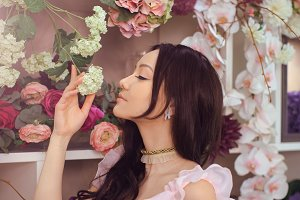 Beautiful asian woman florist in pink dress in flower store