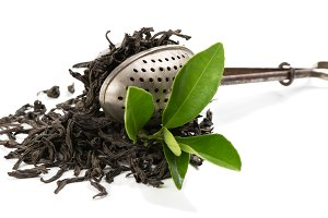 Strainer and dry leaves of tea.