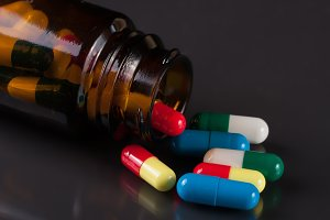 colorful pills in a glass bottle on a dark background