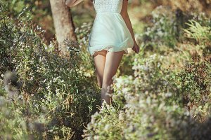 Beautiful young woman happy running in flower medow in forest