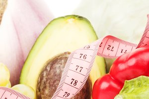 Bell pepper and half of avocado with measuring tape, isolated