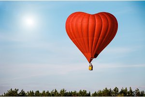 Red air balloon in the shape of a heart flying in blue sky