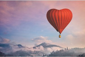 Red air balloon in the shape of a heart flying in morning mountains