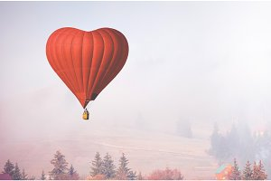 d air balloon in the shape of a heart flying in foggy forest