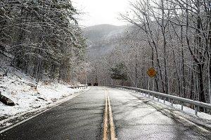 Cars on descent snowy asphalt road