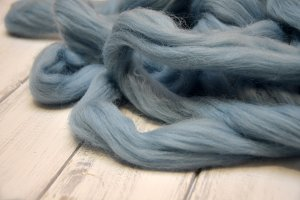 merino wool balls, lying on wooden table, blue thread