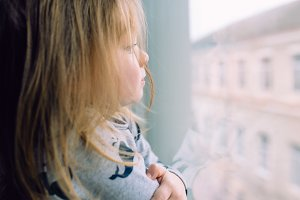 little girl standing near window and looking