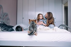 Mother, father,and baby on the bed