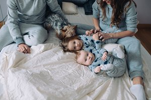 Mother, father, daughter and baby on the bed