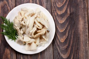 sliced squid on a plate on a dark wooden background