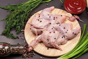 raw chicken carcass with peppercorns and greenery on the cutting board on a dark background