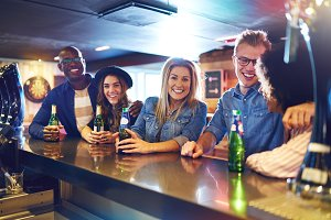 Happy group of people drinking in bar