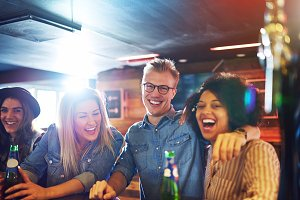 Laughing friends with beer at bar counter