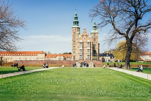 Rosenborg Castle used by Danish regents as a royal residence view from Rosenborg palace garden with green grass anb blue sunny sky at a spring time in Copenhagen, famous Denmark landmark.