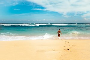 Young fit woman going to swim in colorful sea with sunny blue sky on horizon at Bali island, Indonesia. Outdoor nature landscape of ocean waves and clear white sand beach in Southeast Asia.