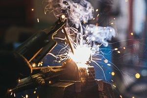 Mechanic man welding metal.