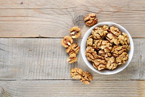 Walnuts in bowl on wooden table