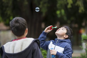 Child blowing soap bubbles outdoors