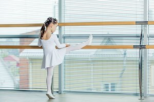 Little ballerina girl. Adorable child dancing classical ballet in a white studio.