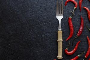 Red chili peppers on a wooden table with a fork, concept, top view