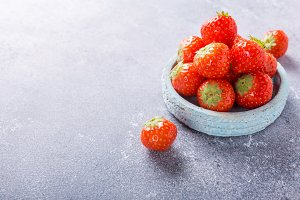 Fresh strawberries on blue plate