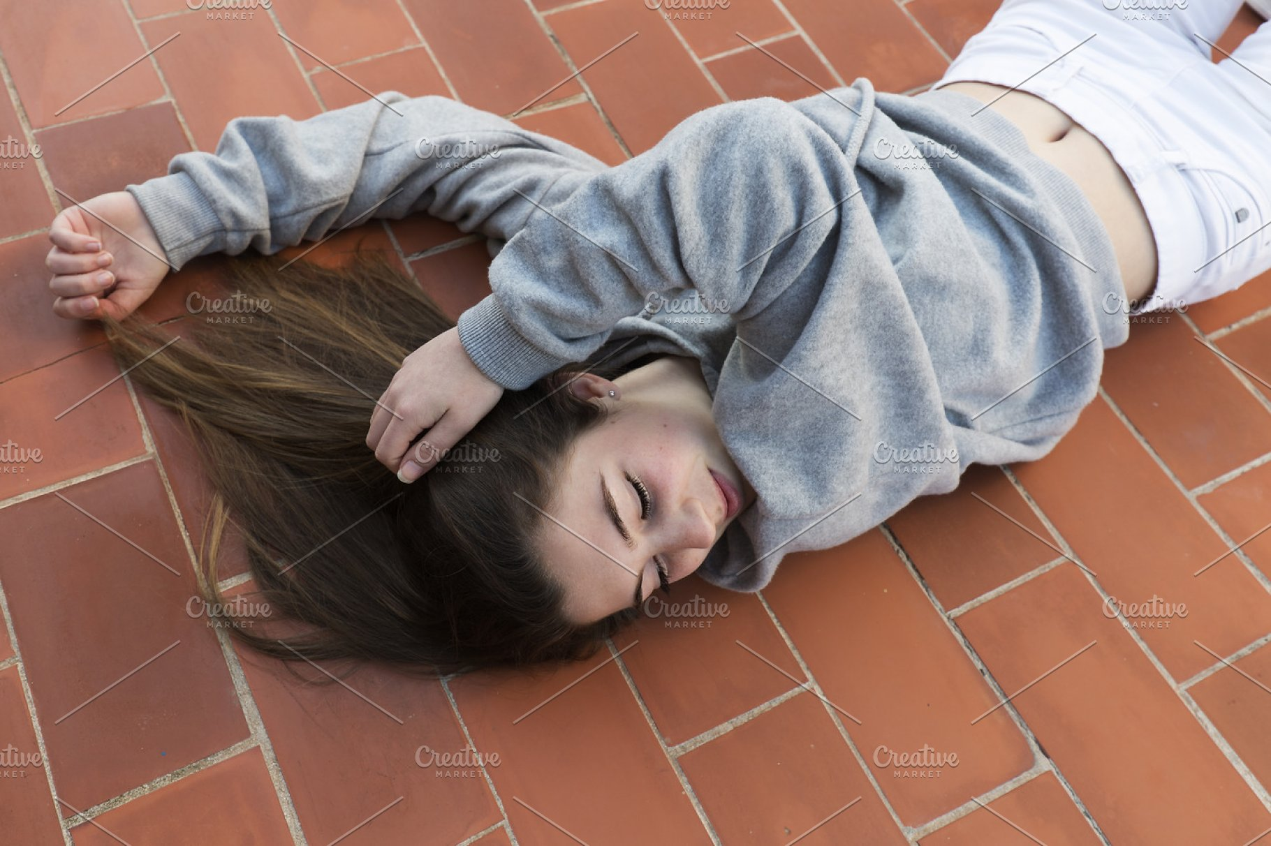 Young woman lying on laid floor. | High