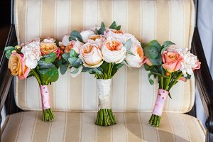 Wedding bouquet on vintage beige chair, peach and white roses