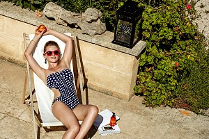 happy modern woman in chaise longue with peach relaxing